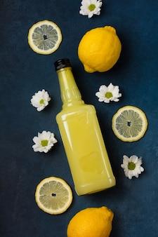 青い背景の上面図にレモンと花とリモンチェッロのボトル