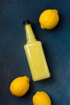 青い背景にレモンとリモンチェッロのボトル