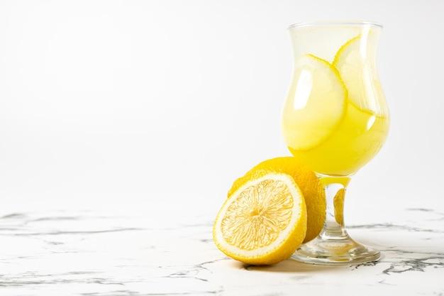 밝은 배경과 대리석 테이블에 있는 아름다운 유리에 레몬을 넣은 리몬첼로 칵테일
