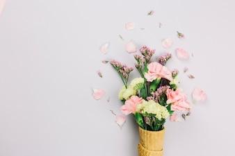 白い背景で隔離のワッフルコーンのリモニウムとカーネーションの花