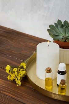Limonium flower with white large lighted candle and essential oil bottle on wooden desk
