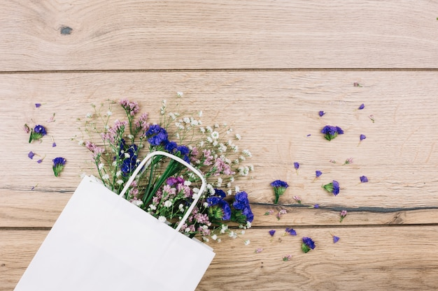 木製の机の上の白い買い物袋の中の紫のlimoniumとgypsophilaの花