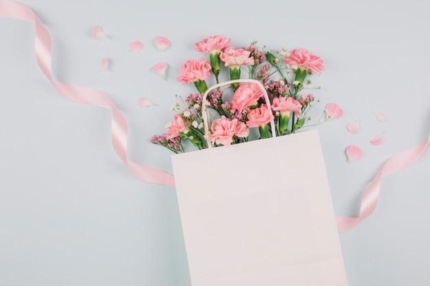 ピンクのカーネーション。白い背景にピンクのリボンと白い買い物袋の中のlimoniumとgypsophilaの花