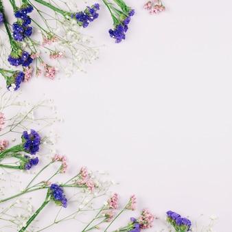 テキストのコピースペースで白い背景に分離された新鮮な美しいlimoniumとgypsophilaの花の俯瞰