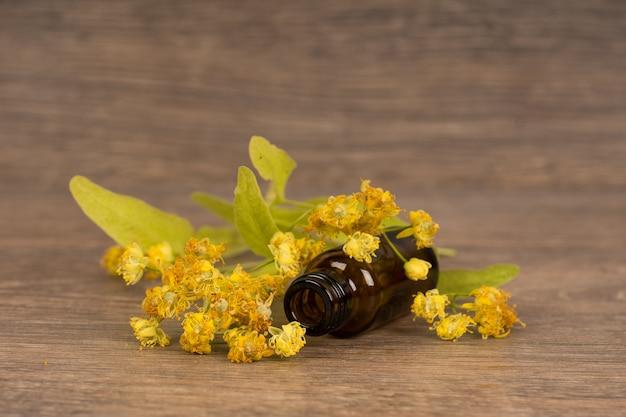 Цветение липы с темно-коричневой стеклянной бутылкой. альтернативная медицина или народная концепция лечения.