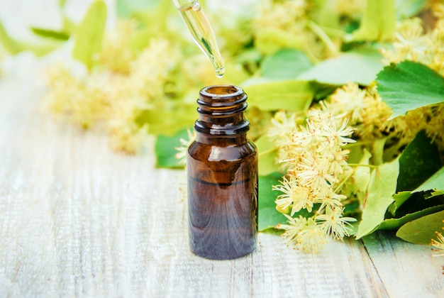 Linden extract and flowers in a small bottle. selective focus.