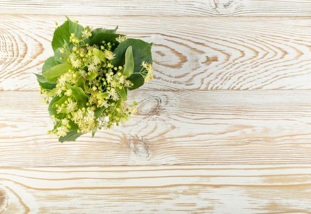 木製のテーブルの上のリンデンの花。木製のテーブルの上の美しい夏の花束。ティリアブロッサム