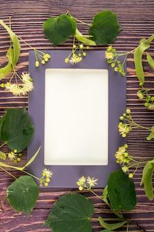 木製のテーブルにフレームとリンデンの花。木製のテーブルの上の美しい夏の花束