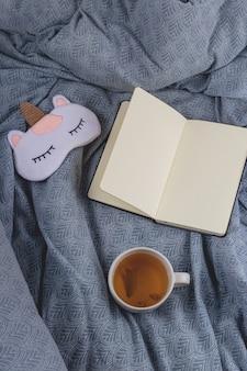 本と睡眠マスクの隣のベッドで健康的な睡眠のためのリンデンティー