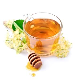 花と白い背景で隔離の蜂蜜とリンデンティー