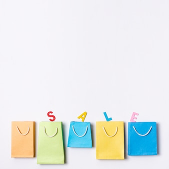 Line of coloured paper bags with sale text concept