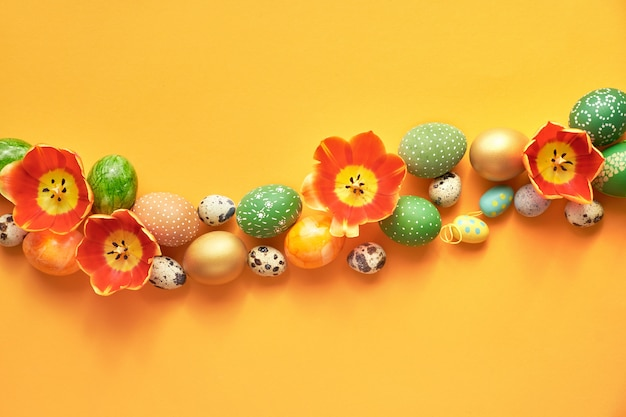 Line or curved border made of tulip flowers and easter eggs. easter flat lay on orange paper.