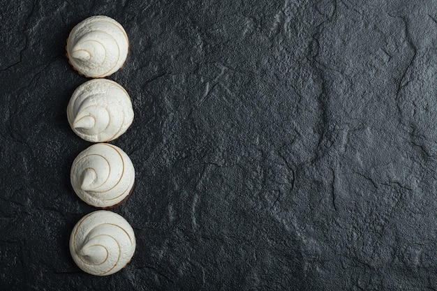 A line of delicious cupcakes on a dark background.