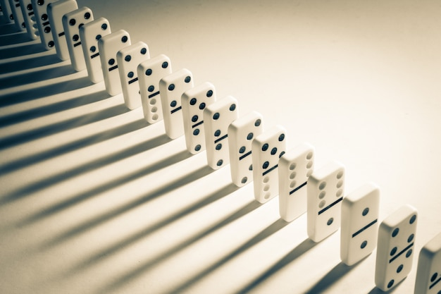 Line of dominoes stacked neatly with shadows
