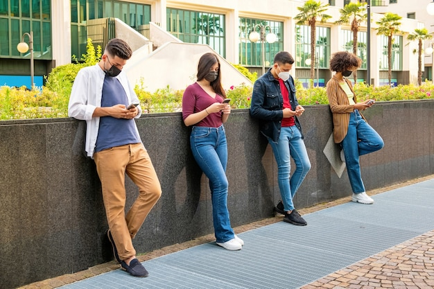 Line of friends ignoring each other to text on their mobile phones as they relax in an urban street leaning against a wall wearing protective face masks during the covid-19 pandemic