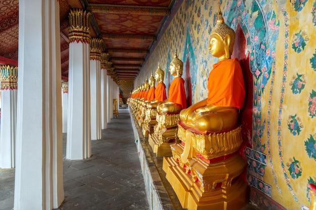 Line of golden buddha statue along wall at wat arun.