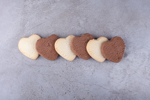 Line of heart shaped cookies placed on a stone background .