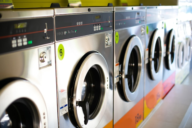 Line of industrial washing machines in a public laundromat.