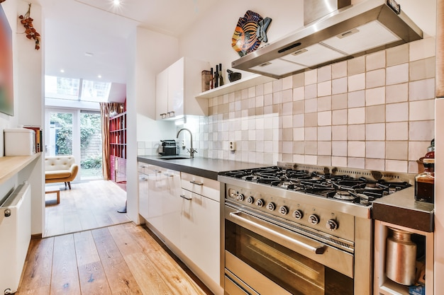 Line kitchen with white cabinets and black counter with big gas stove in modern apartment