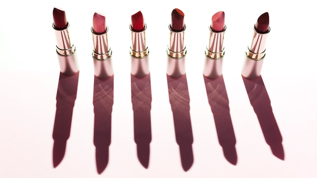 Line of metallic lipsticks on pink background