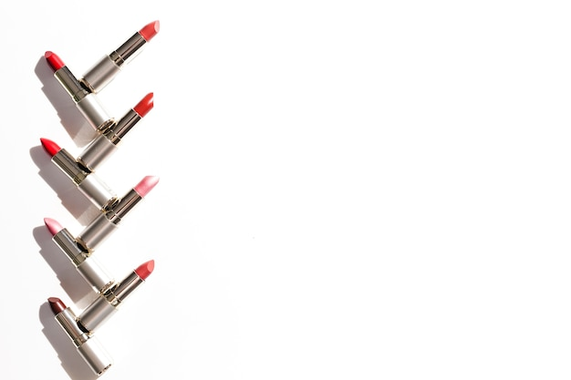 Line of metallic lipsticks on white background