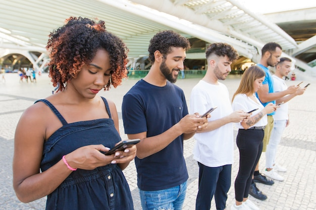 Line of mix raced people texting messages on smartphones