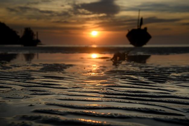 日没時間の低い暗い照明とビーチの砂のライン。