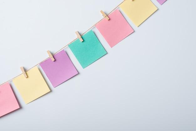 Линия красочных заметок на веревке с булавками для одежды