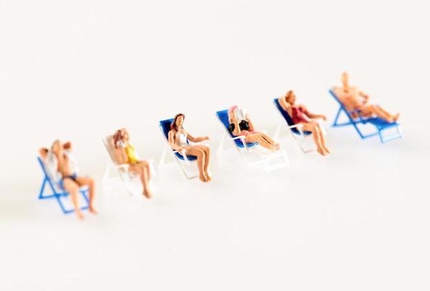 갑판 의자에 편안한 미니어처 사람들의 라인