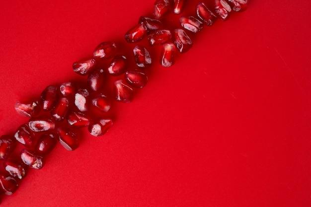 루비 잘 익은 신선한 육즙이 많은 석류 씨앗은 복사 공간이 있는 빨간색 배경에 격리되어 있습니다.