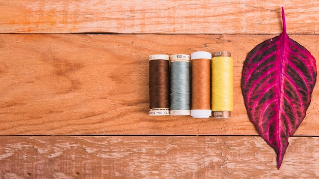 Line of reel of yarn on wooden background