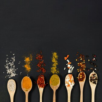 Line of wooden spoons full of spices