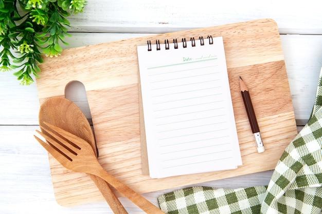 木製のフォークとspでカッティングボードとテーブルクロスを切り刻むメモ帳紙を並べ替え
