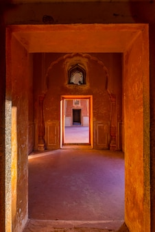 Lined doors and passages in orange toned corridor with decorated walls