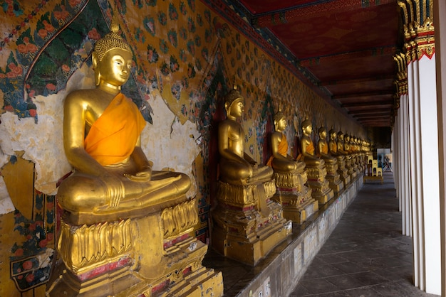 Lined golden buddha statues in wat arun