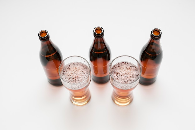 Lined up beer bottles and glasses on white background