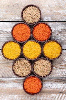 Lined up different lentils in a brown bowls top view on a beige wooden table