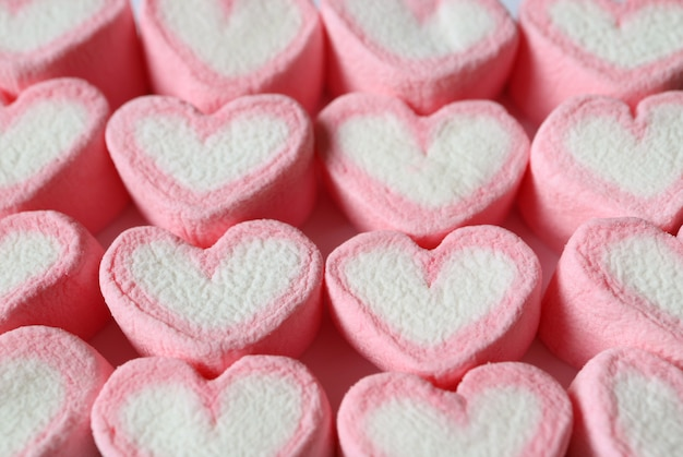 Lined up pastel pink and white heart shaped marshmallow candies for background