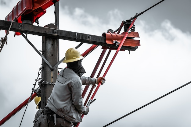 The lineman are replacing damaged insulator insulators by using insulated wire-tong sets