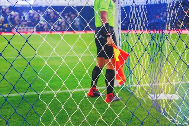 Lineman помощник рефери, проверяющий сетку ворот в футболе перед началом игры.