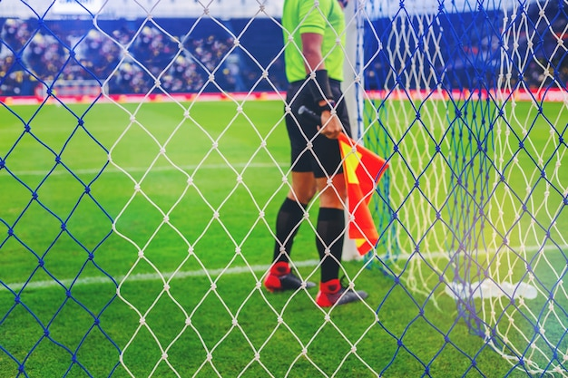 Lineman assistant referee checking a net of goal in soccer field before game start.