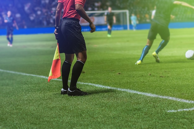 Lineman assistant referee with flag officiate soccer game beside soccer field.