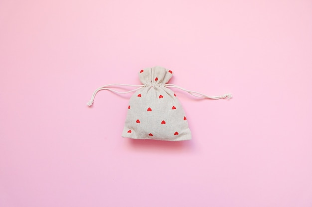 Linen bag with red hearts on pink background.