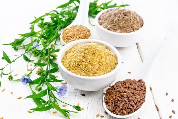 2つのボウルにリネンのふすまと小麦粉、スプーンの種、亜麻の葉と白い木の板の背景に花