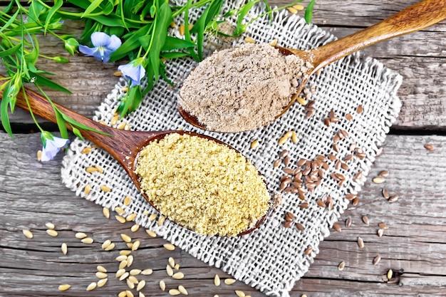 上から木の板の背景に黄麻布ナプキン、亜麻の葉と花の2つのスプーンでリネンふすまと小麦粉