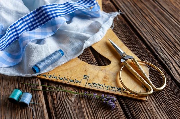 Льняная ткань, нитки, ножницы и шаблон линейки для пошива одежды. натуральная льняная ткань, пошив одежды, медленная мода.