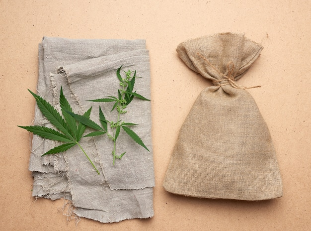 Linen, green hemp leaf, brown bag on a brown wooden background