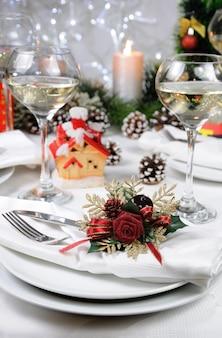 Салфетка льняная, украшенная рождественским корсажем на столе