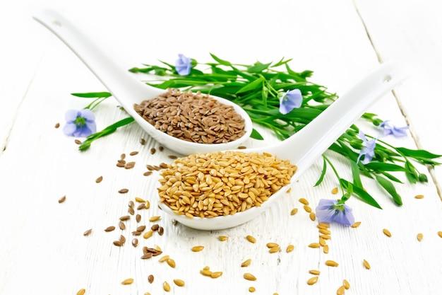 リネンは2つのスプーンで白と茶色、亜麻の茎と青い花と白い木の板の背景の葉