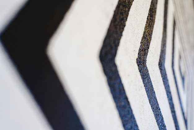 Lines like black arrows on white background painted on a wall indicating direction.